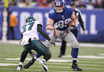 EAST RUTHERFORD, NJ - DECEMBER 19:  Kevin Boss #89 of the New York Giants eludes the tackle of Quintin Mikell #27 of the Philadelphia Eagles during their game on December 19, 2010 at The New Meadowlands Stadium in East Rutherford, New Jersey.  (Photo by A