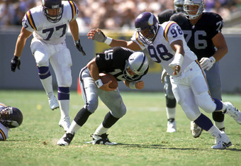 Esera Tuaolo, pictured here with the Minnesota Vikings, sacks Raiders quarterback Jeff Hostetler.
