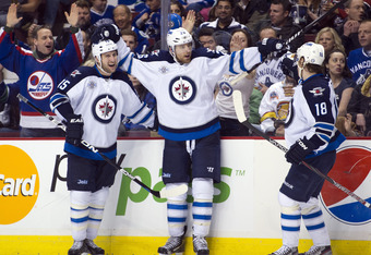 VANCOUVER, CANADA - MARCH 8: Blake Wheeler #26 of the Winnipeg Jets celebrates with Tanner Glass #15 and Bryan Little #18 after scoring against the Vancouver Canucks during the third period in NHL action on March 08, 2012 at Rogers Arena in Vancouver, Bri