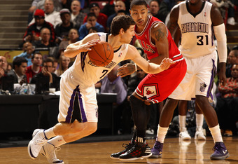 SACRAMENTO, CA - DECEMBER 29:  Jimmer Fredette #7 of the Sacramento Kings dribbles around Derrick Rose #1 of the Chicago Bulls at Power Balance Pavilion on December 29, 2011 in Sacramento, California. NOTE TO USER: User expressly acknowledges and agrees t