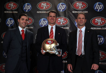 SAN FRANCISCO, CA - JANUARY 07:  Jim Harbaugh poses for a picture with President and CEO of the San Francisco 49ers, Jed York, (left) and general manager Trent Baalk following a press conference where Harbaugh was introduced as the new San Francisco 49ers