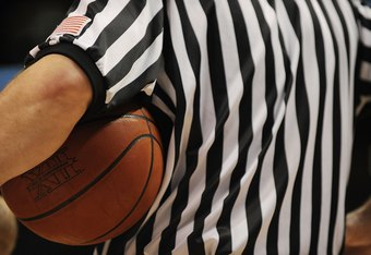 What uniform best describes the approach officials should take when calling games, high school and NCAA basketball's black and white stripes or the NBA's grey shirt?
