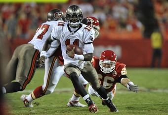 KANSAS CITY, MO - AUGUST 12:  Quarterback Josh Johnson #11 of the Tampa Bay Buccaneers rushes up field for a first down past line backer Eric Bakhtiari #66 of the Kansas City Chiefs during the first half on August 12, 2011 at Arrowhead Stadium in Kansas C