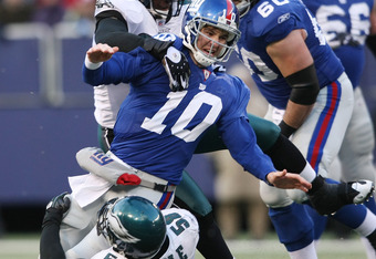 EAST RUTHERFORD, NJ - DECEMBER 07:  Eli Manning #10 of the New York Giants is tackled by Darren Howard #90 and Trent Cole #58 of the Philadelphia Eagles at Giants Stadium on December 7, 2008 in East Rutherford, New Jersey.  (Photo by Nick Laham/Getty Imag