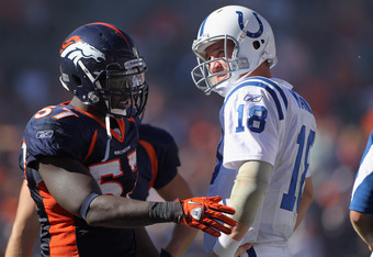 DENVER - SEPTEMBER 26:  Quarterback Peyton Manning #18 of the Indianapolis Colts and linebacker Mario Haggan #57 of the Denver Broncos talk during a video replay ruling at INVESCO Field at Mile High on September 26, 2010 in Denver, Colorado. The Colts def
