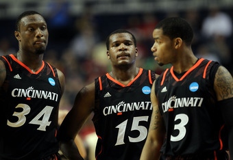 NASHVILLE, TN - MARCH 18:  Yancy Gates #34 of the Cincinnati Bearcats looks on with Jermaine Sanders #15 and Dion Dixon #3 against the Florida State Seminoles during the third round of the 2012 NCAA Men's Basketball Tournament at Bridgestone Arena on Marc