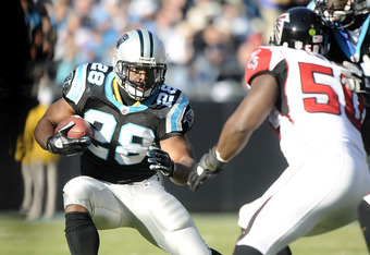 CHARLOTTE, NC - DECEMBER 11:  Jonathan Stewart #28 of the Carolina Panthers tries to avoid Curtis Lofton #50 of the Atlanta Falcons at Bank of America Stadium on December 11, 2011 in Charlotte, North Carolina.  (Photo by Jared C. Tilton/Getty Images)