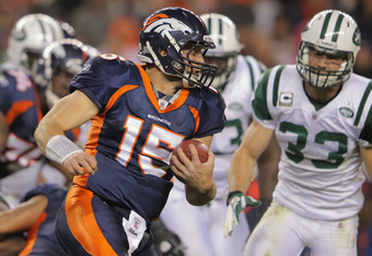 DENVER, CO - NOVEMBER 17:  Quarterback Tim Tebow #15 of the Denver Broncos rushes against Eric Smith #33 of the New York Jets at Sports Authority Field at Mile High on November 17, 2011 in Denver, Colorado. The Broncos defeated the Jets 17-13.  (Photo by