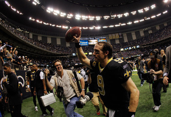 NEW ORLEANS, LA - JANUARY 07:   Drew Brees #9 of the New Orleans Saints holds the ball in the air as he runs off the field after defeating the Detroit Lions by a score of 45-28 to win during their 2012 NFC Wild Card Playoff game at Mercedes-Benz Superdome