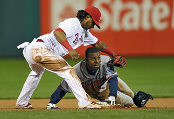 PHILADELPHIA, PA - SEPTEMBER 06: Michael Bourn #24 of the Atlanta Braves is safe at second base on a late tag by Michael Martinez #19 of the Philadelphia Phillies in the seventh inning at Citizens Bank Park on September 6, 2011 in Philadelphia, Pennsylvan