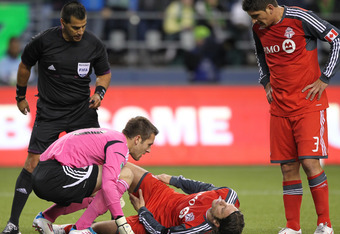 SEATTLE, WA - MARCH 17:  Goalkeeper Milos Kocic #30 and Miguel Aceval #3 of Toronto FC check on Torsten Frings #22 after he injured his leg making a tackle against the Seattle Sounders at CenturyLink Field on March 17, 2012 in Seattle, Washington. (Photo