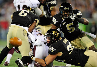 NASHVILLE, TN - DECEMBER 30:  Robert Elliott #2 of the Mississippi State Bulldogs fumbles after being hit by Kenny Okoro #6, Scott Betros #32 and Chyl Quarles #5 of the Wake Forest Demon Deacons during play at the Franklin American Mortgage Music City Bow