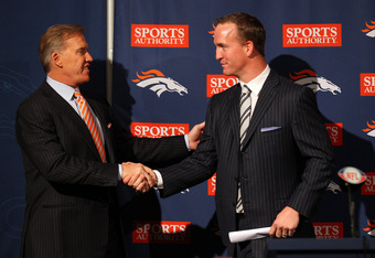 ENGLEWOOD, CO - MARCH 20:  Quarterback Peyton Manning (R) shakes hands with executive vice president of football operations John Elway during a news conference announcing Manning's contract with the Denver Broncos in the team meeting room at the Paul D. B