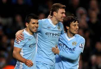 MANCHESTER, ENGLAND - FEBRUARY 25:  Edin Dzeko of Manchester City celebrates scoring his team's third goal with team mates Sergio Aguero (L) and David Silva (R) during the Barclays Premier League match between Manchester City and Blackburn Rovers at the E