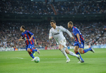 MADRID, SPAIN - MARCH 14:  Cristiano Ronaldo (C) of Real Madrid runs past Vasili Berezutski (#24) and Sergei Ignashevich of PFC CSKA Moskva during the UEFA Champions League Round of 16 second leg match between Real Madrid and PFC CSKA Moskva at estadio Sa