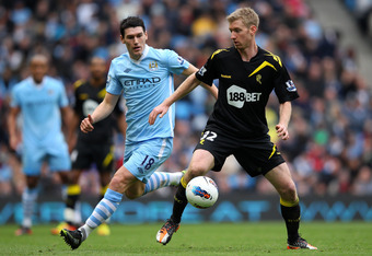 MANCHESTER, ENGLAND - MARCH 03:  Tim Ream of Bolton Wanderers holds off a challenge from Gareth Barry of Manchester City during the Barclays Premier League match between Manchester City and Bolton Wanderers at the Etihad Stadium on March 3, 2012 in Manche