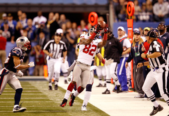 INDIANAPOLIS, IN - FEBRUARY 05:  Mario Manningham #82 of the New York Giants makes a catch on the sidelines against Patrick Chung #25 (L) and Sterling Moore #29 (obscured) of the New England Patriots for a gain of 39 yards in the fourth quarter during Sup