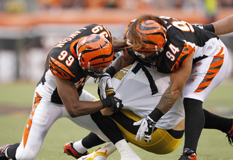CINCINNATI, OH - NOVEMBER 13: Ben Roethlisberger #7 of the Pittsburgh Steelers gets sacked by Manny Lawson #99 and Domata Peko #94 of the Cincinnati Bengals at Paul Brown Stadium on November 13, 2011 in Cincinnati, Ohio. The Steelers won 24-17. (Photo by