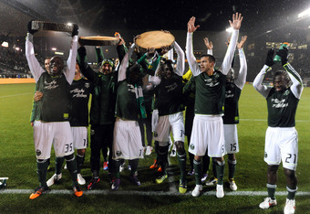 PORTLAND, OR - MARCH 12: Members of the Portland Timbers hold up log slabs representing the goals scored as celebrate after the game against the Philadelphia Union at JELD-WEN Field on March 12, 2012 in Portland, Oregon. The Timbers won the game 3-1. (Pho