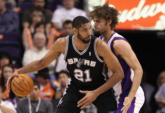 PHOENIX, AZ - APRIL 13:  Tim Duncan #21 of the San Antonio Spurs handles the ball under pressure from Robin Lopez #15 of the Phoenix Suns during the NBA game at US Airways Center on April 13, 2011 in Phoenix, Arizona.  NOTE TO USER: User expressly acknowl