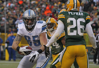 GREEN BAY, WI - JANUARY 01:  Tony Scheffler #85 of the Detroit Lions catches a touchdown pass between Jarrett Bush #24 and Charlie Peprah #26 of the Green Bay Packers at Lambeau Field on January 1, 2012 in Green Bay, Wisconsin. The Packers defeated the Li