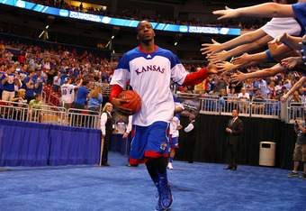 ST LOUIS, MO - MARCH 25:  Tyshawn Taylor #10 of the Kansas Jayhawks greets fans as he runs out to the court to play against the North Carolina Tar Heels during the 2012 NCAA Men's Basketball Midwest Regional Final at Edward Jones Dome on March 25, 2012 in