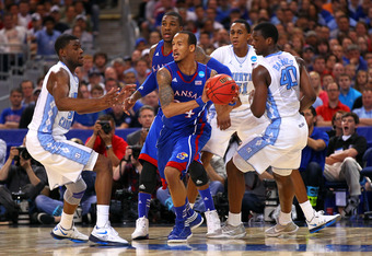 ST LOUIS, MO - MARCH 25:  Travis Releford #24 of the Kansas Jayhawks looks to pass against Reggie Bullock #35 and Harrison Barnes #40 of the North Carolina Tar Heels during the 2012 NCAA Men's Basketball Midwest Regional Final at Edward Jones Dome on Marc