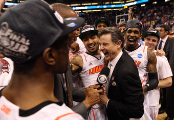 PHOENIX, AZ - MARCH 24:  Head coach Rick Pitino celebrates with the Louisville Cardinals before he gets interviewed by Reggie Miller after the Cardinals defeat the Florida Gators 72-68 during the 2012 NCAA Men's Basketball West Regional Final at US Airway