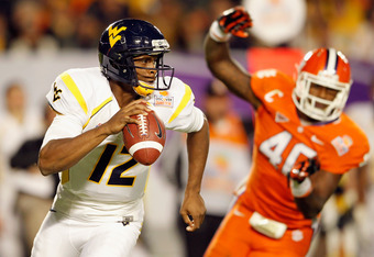 MIAMI GARDENS, FL - JANUARY 04:  Geno Smith #12 of the West Virginia Mountaineers rolls out of the pocket against Andre Branch #40 of the Clemson Tigers during the Discover Orange Bowl at Sun Life Stadium on January 4, 2012 in Miami Gardens, Florida.  (Ph