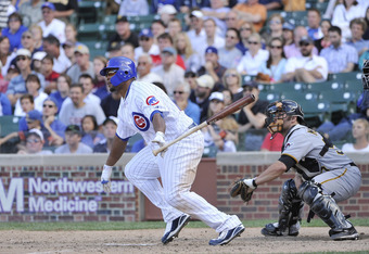 CHICAGO, IL - SEPTEMBER 04:  Marlon Byrd #24 of the Chicago Cubs follows through on an RBI single scoring teammate Carlos Pena #22 as catcher Michael McKenry #55 of the Pittsburgh Pirates watches during the eighth inning at Wrigley Field on September 4, 2