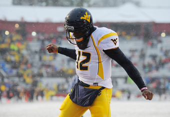 NEW BRUNSWICK, NJ - OCTOBER 29:  Geno Smith #12 of the West Virginia Mountaineers celebrates after Shawne Alston #20 of the Mountaineers scored a touchdown against the Rutgers Scarlet Knights at High Point Solutions Stadium on October 29, 2011 in New Brun