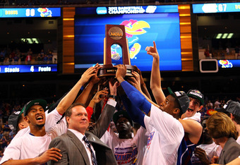 ST LOUIS, MO - MARCH 25: (L-R) Travis Releford #24, head coach Bill Self, Tyshawn Taylor #10, Thomas Robinson #0 and Jeff Withey #5 of the Kansas Jayhawks celebrate with the Midwest Final Championship trophy after they won 80-67 against theNorth Carolina