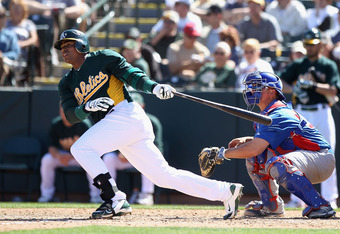 PHOENIX, AZ - MARCH 20:  Yoenis Cespedes #52 of the Oakland Athletics hits a single against the Chicago Cubs during the spring training game at Phoenix Municipal Stadium on March 20, 2012 in Phoenix, Arizona.  (Photo by Christian Petersen/Getty Images)