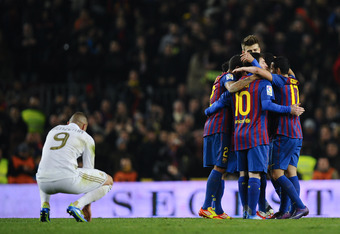 BARCELONA, SPAIN - JANUARY 25:  Karim Benzema of Real Madrid (L) looks on dejected as FC Barcelona players celebrate the victory at the end the Copa del Rey quarter final second leg match between FC Barcelona and Real Madrid at Camp Nou on January 25, 201