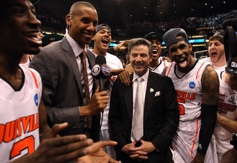 PHOENIX, AZ - MARCH 24:  Head coach Rick Pitino celebrates with the Louisville Cardinals as he gets interviewed by Reggie Miller after the Cardinals defeat the Florida Gators 72-68 during the 2012 NCAA Men's Basketball West Regional Final at US Airways Ce