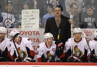WINNIPEG, CANADA - MARCH 26: Ottawa Senators' head coach Paul MacLean watches action from the jumbotron as Winnipeg fans show a sign for him in NHL action at the MTS Centre on March 26, 2012 in Winnipeg, Manitoba, Canada. (Photo by Marianne Helm/Getty Ima