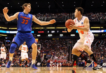 PHOENIX, AZ - MARCH 24:  Kyle Kuric #14 of the Louisville Cardinals looks to shoot over Erik Murphy #33 of the Florida Gators in the first half during the 2012 NCAA Men's Basketball West Regional Final at US Airways Center on March 24, 2012 in Phoenix, Ar