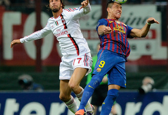 MILAN, ITALY - MARCH 28:  Luca Antonini #77 of AC Milan and Alexis Sanchez #9 of Barcelona compete for the ball during the UEFA Champions League quarter final first leg match between AC Milan and Barcelona at Stadio Giuseppe Meazza on March 28, 2012 in Mi