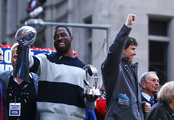 NEW YORK, NY - FEBRUARY 07:  Defensive end Justin Tuck (L) of the New York Giants holds the Vince Lombardi Trophy next to quarterback Eli Manning during the New York Giants' ticker tape victory parade down the Canyon of Heros on February 7, 2012 in New Yo