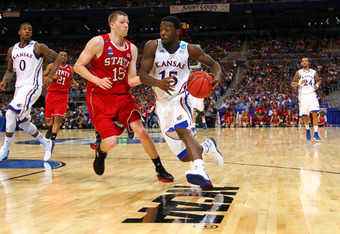ST. LOUIS, MO - MARCH 23:  Elijah Johnson #15 of the Kansas Jayhawks drives in the second half against Scott Wood #15 of the North Carolina State Wolfpack during the 2012 NCAA Men's Basketball Midwest Regional Semifinal at Edward Jones Dome on March 23, 2