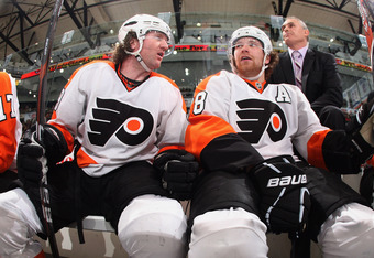 UNIONDALE, NY - MARCH 15:  (L-R) Scott Hartnell #19 and Claude Giroux #28 of the Philadelphia Flyers watch from the bench during the game against the New York Islanders at the Nassau Veterans Memorial Coliseum on March 15, 2012 in Uniondale, New York.  Th