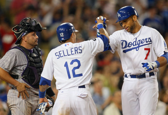 LOS ANGELES, CA - AUGUST 26:  James Loney #7 and Justin Sellers #12 of the Los Angeles Dodgers celebrate at home plate after Loney hit a two-run home run in the seventh inning as catcher Eliezer Alfonzo #55 of the Colorado Rockies looks on during the MLB