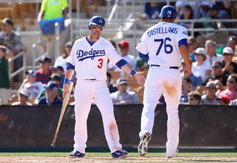 GLENDALE, AZ - MARCH 08:  Adam Kennedy #3 of the Los Angeles Dodgers high fives Alex Castellanos #76 after he scored a run against the Oakland Athletics during the spring training game at Camelback Ranch on March 8, 2012 in Glendale, Arizona.  (Photo by C