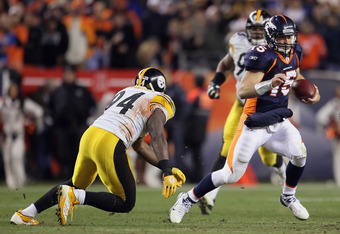 DENVER, CO - JANUARY 08:  Quarterback Tim Tebow #15 of the Denver Broncos eludes a tackle from  Lawrence Timmons #94 of the Pittsburgh Steelers during the AFC Wild Card Playoff game at Sports Authority Field at Mile High on January 8, 2012 in Denver, Colo