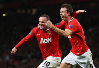 MANCHESTER, ENGLAND - MARCH 26:  Wayne Rooney of Manchester United (L) celebrates with Jonny Evans as he scores their first goal during the Barclays Premier League match between Manchester United and Fulham at Old Trafford on March 26, 2012 in Manchester,