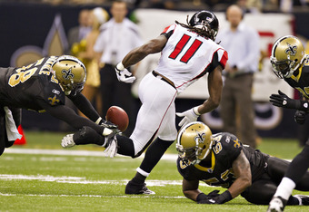 NEW ORLEANS, LA - DECEMBER 26:   Julio Jones #11 of the Atlanta Falcons fumbles the ball after catching a pass against the New Orleans Saints at Mercedes-Benz Superdome on December 26, 2011 in New Orleans, Louisiana.  The Saints defeated the Falcons 45-16