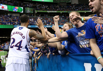 NEW ORLEANS, LA - MARCH 31:  Travis Releford #24 of the Kansas Jayhawks celebrates with fans after defeating the Ohio State Buckeyes 64-62 in the National Semifinal game of the 2012 NCAA Division I Men's Basketball Championship at the Mercedes-Benz Superd