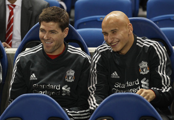 BRIGHTON, ENGLAND - SEPTEMBER 21:  Steven Gerrard of Liverpool jokes with team mate Jonjo Shelvey as they sit on the bench prior to the Carling Cup Third Round match between Brighton & Hove Albion and Liverpool at the American Express Community Stadium on
