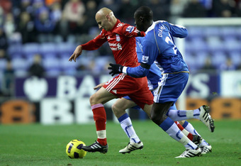 WIGAN, ENGLAND - NOVEMBER 10:  Jonjo Shelvey of Liverpool attempts to move away from Mohammed Diame of Wigan Athletic during the Barclays Premier League match between Wigan Athletic and Liverpool at DW Stadium on November 10, 2010 in Wigan, England.  (Pho