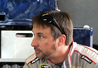 DAYTONA BEACH, FL - FEBRUARY 22:  David Reutimann, driver of the #93 BK Racing Toyota, sits in the garage during practice for the NASCAR Sprint Cup Series Daytona 500 at Daytona International Speedway on February 22, 2012 in Daytona Beach, Florida.  (Phot